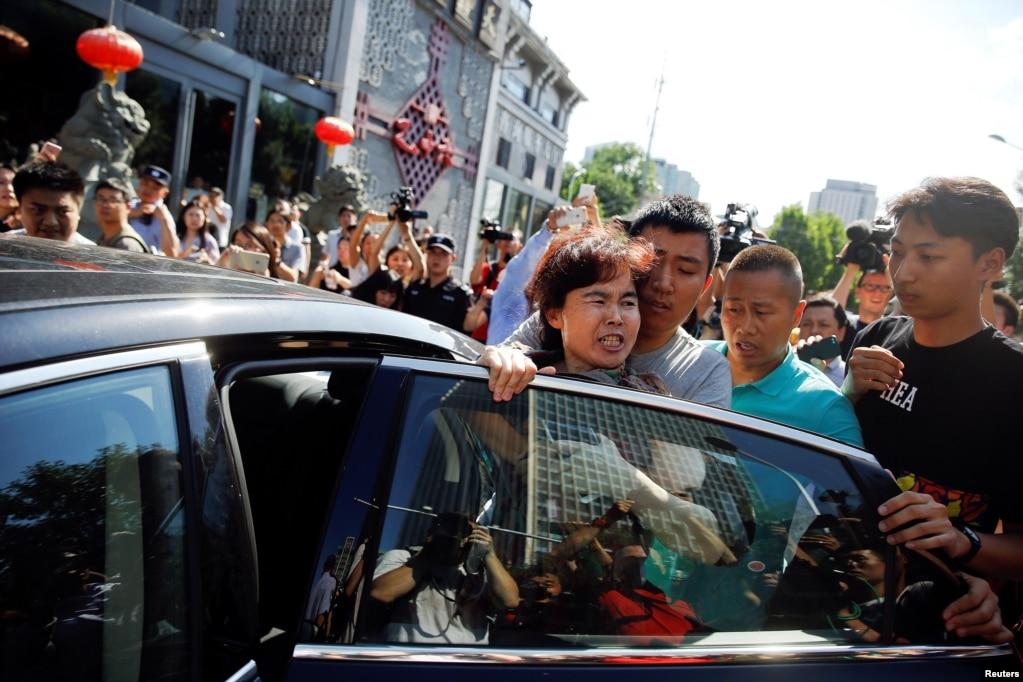 一名婦女在與一群記者談論她目睹的美國駐北京大使館外爆炸案後被警察抓住,塞進一輛汽車。 (2018年7月26日)