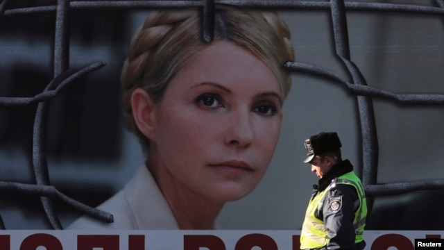 An Interior Ministry officer walks past a board displaying a portrait of jailed former Ukrainian Prime Minister and opposition leader Yulia Tymoshenko at a protest tent camp set up by her supporters in central Kyiv, Nov. 18, 2013.