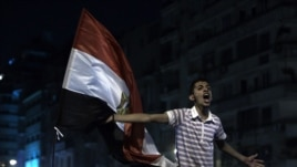 A youth shouts next to an Egyptian flag as the revolutionary youth of Egypt return to Tahrir to protest the outcome of the Egyptian presidential election, Cairo, Egypt, May 28, 2012.