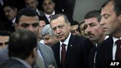 Turkish prime minister Recep Tayyip Erdogan, center surrounded by his bodyguards, leaves after his meeting with Grand Sheik of Al Azhar Ahmed el-Tayyib, unseen, at his office in Cairo, Egypt Tuesday, Sept. 13, 2011. Erdogan, intent on broadening Turkey's