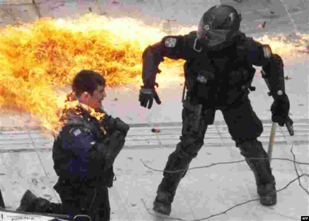 A motorcycle policeman burns as his colleague, left, tries to help him after protesters threw a petrol bomb in Athens, Wednesday, Feb. 23, 2011. Scores of youths hurled rocks and petrol bombs at riot police after clashes broke out Wednesday during a mass