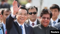 Chinese Premier Li Keqiang waves as he is received by Indian junior minister for external affairs, E. Ahamed, right, after he arrived in New Delhi, India, May 19, 2013.