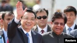 PM China Li Keqiang melambaikan tangan kepada para wartawan setibanya di New Delhi, India (19/5).