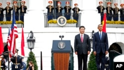 President Barack Obama and Chinese President Xi Jinping stand at attention for the playing of each counties national anthem during an official state arrival ceremony for the Chinese president, Sept. 25, 2015.