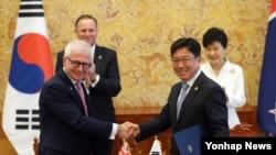박근혜 대통령과 존 키 뉴질랜드 총리가 참석한 가운데 23일 청와대에서 한-뉴질랜드 협정서명식이 열렸다. 윤상직 산업자원부 장관(오른쪽)과 티모시 그로서 통상장관이 양국 자유무역협정(FTA) 협정문과 부속서에 서명한 뒤 악수하고 있다.