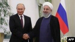 El presidente ruso, Vladimir Putin (izq.),y el presidente iraní, Hassan Rouhani, se dan la mano durante la reunión, en Teherán.