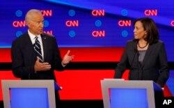 លោកស្រី Kamala Harris កំពុងស្ដាប់អតីតអនុប្រធានាធិបតី Joe Biden ថ្លែងក្នុងការជជែកដេញដោលគ្នាបឋមដែលរៀបចំដោយទូរទស្សន៍ CNN កាលពីថ្ងៃទី៣១ កក្កដា ២០១៩។