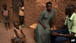 """In this Sept. 10, 2019 photo, Janvier Ngabonziza, right, interviews Lyiza Uwimbabazi about her sister who passed away recently during a """"verbal autopsy"""" in Rwamagana, Rwanda."""