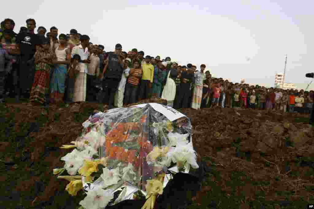 Hundreds of Bangladeshi mourners watch as the bodies of victims of Saturday's fire in a garment factory are buried in Dhaka, Bangladesh, November 27, 2012.