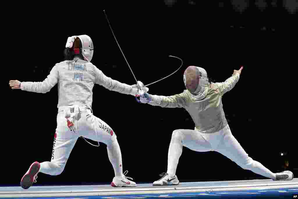 Misaki Emura of Japan, left, and Amira Ben Chaabane of Tunisia compete in the women's Sabre team round of 16 competition at the 2020 Summer Olympics, Saturday, July 31, 2021, in Chiba, Japan. (AP Photo/Hassan Ammar)