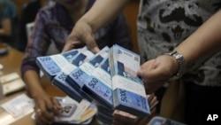 Seorang pegawai tempat penukaran uang di Jakarta memegang beberapa bundel uang rupiah. (Foto: Dok)