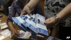 Seorang pegawai tempat pertukaran mata uang di Jakarta menghitung uang rupiah (Foto: dok).