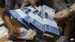 Seorang petugas sedang menghitung jumlah uang rupiah di kantor penukaran mata uang asing di Jakarta (Foto: dok).