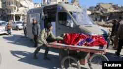 បុរសម្នាក់រុញរទេះដែលមានស្រ្តីម្នាក់ដេកនៅលើនោះ ខណៈដែលរថយន្តចាំជម្លៀសមនុស្សចេញពីតំបន់កាន់កាប់ដោយក្រុមឧទ្ទាមក្នុងក្រុង Aleppo ប្រទេសស៊ីរី កាលពីថ្ងៃទី១៥ ខែធ្នូ ឆ្នាំ២០១៦។