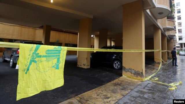 A Hezbollah flag is seen near the crime scene where commander Hasan al-Laqqis was killed in the southern Hadath district in Beirut, Dec. 4, 2013.