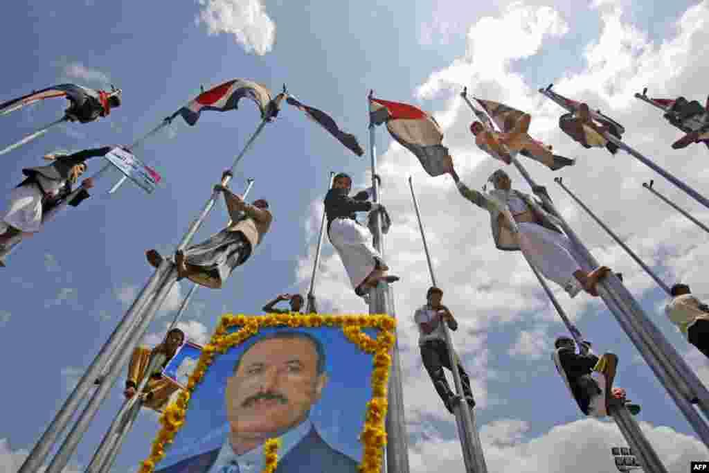 Supporters of Yemen's President Ali Abduallah Saleh stand on flag poles celebrating his return to Sanaa, Yemen, Friday, Sept. 23, 2011. (AP Photo/Hani Mohammed)