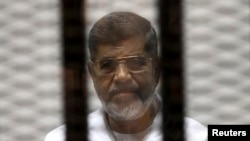 FILE - Ousted Egyptian President Mohamed Morsi is seen behind bars during his trial at a court in Cairo May 8, 2014.