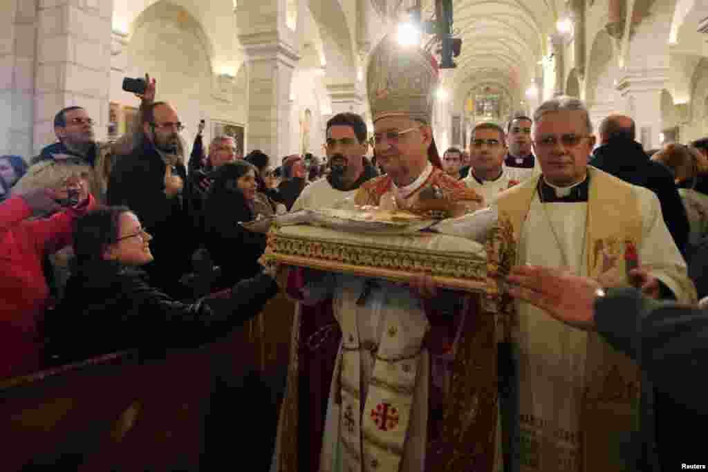 O Patriarca Latino de Jerusalém, Fouad Twal (2º à direita) transporta uma estatueta do menino Jesus na Missa de Natal, à meia-noite, na Igreja de Santa Catarina, que está ligada à Igreja da Natividade, na cidade de Bank em Belém.