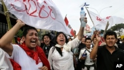 Students celebrate outside Congress after a new labor law affecting young workers was repealed by lawmakers in Lima, Peru, Jan. 26, 2015.