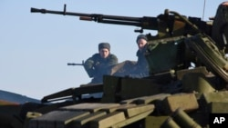 Pro-Russia separatists sit atop a tank at a checkpoint north of Luhansk, eastern Ukraine, Jan. 14, 2015.