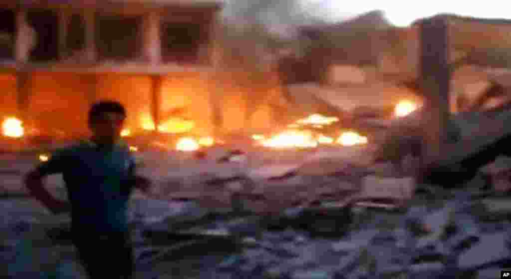 This image taken from video obtained from the Shaam News Network shows a Syrian man walking near destruction and fire caused by a bomb that hit Binnish town, Idlib province, Sept. 5, 2013.