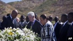 Haiti's President Michel Martelly, left, and UN special envoy to Haiti and former President Bill Clinton attend memorial in Haiti, Jan. 12, 2013