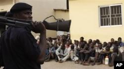 Yan sanda na kaiwa da komowa a wajen wata kotun shari'a inda ake shari'ar wadanda ake zargi nada hannu wajen shirya tarzoma kafin a fara sauraren shari'arsu a Kaduna, Nigeria.
