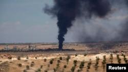 Asap membubung di daerah Hilan, Suriah, akibat pertempuran di daerah tersebut (21/5). (Reuters/George Ourfalian)