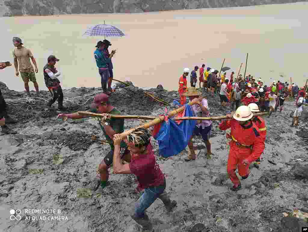 In this photo released from Myanmar Fire Service Department, rescuers carry a recovered body of a victim of a landslide from a jade mining area in Hpakant, Kachin state, northern Myanmar.