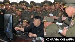 Lãnh tụ Bắc Triều Tiên Kim Jong-Un xem một cuộc tập trận pháo kích của đơn vị pháo binh trên máy tính cùng các giới chức quân đội (Ảnh tư liệu do thông tấn xã Bắc Triều Tiên KCNA phát hành).