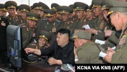 North Korean leader Kim Jong Un, center, looks at a computer as he inspects a shelling drill of a long-range artillery.