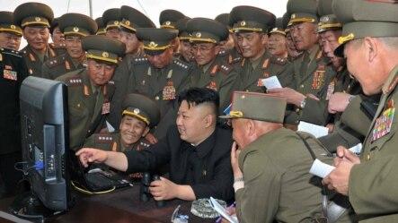 在军事演习中,朝鲜领导人金正恩在电脑前对军官们讲解