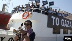 "Para aktivis pro-Palestina membawa poster 'Free Gaza' di atas kapal bantuan ""Audacity of Hope"" di pelabuhan Athena, Yunani (30/6)."