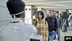 Petugas kesehatan memeriksa penumpang yang baru tiba di bandara Chandra Bose, Kolkata, India, Selasa (21/1) untuk mendeteksi kemungkinan terjangkit virus corona.