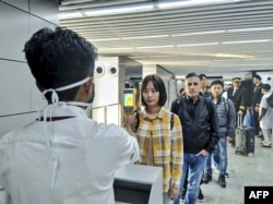 In this handout photograph taken and released by the Ministry of Civil Aviation (MoCA) on January 21, 2020, a man (L) uses a thermographic camera to screen the head of people at Netaji Subhash Chandra Bose International Airport in Kolkata