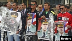 Protesters hold posters of Sylejman Selimi, a war commander during the 1998-1999 war, during a protest against a parliamentary vote to create a new war crimes court, in Pristina, Kosovo, May 29, 2015.