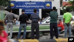 Journalists wait in front of Cambodia National Rescue Party (CNRP) during the party's meeting, in Phnom Penh, Cambodia, Thursday, May 26, 2016.