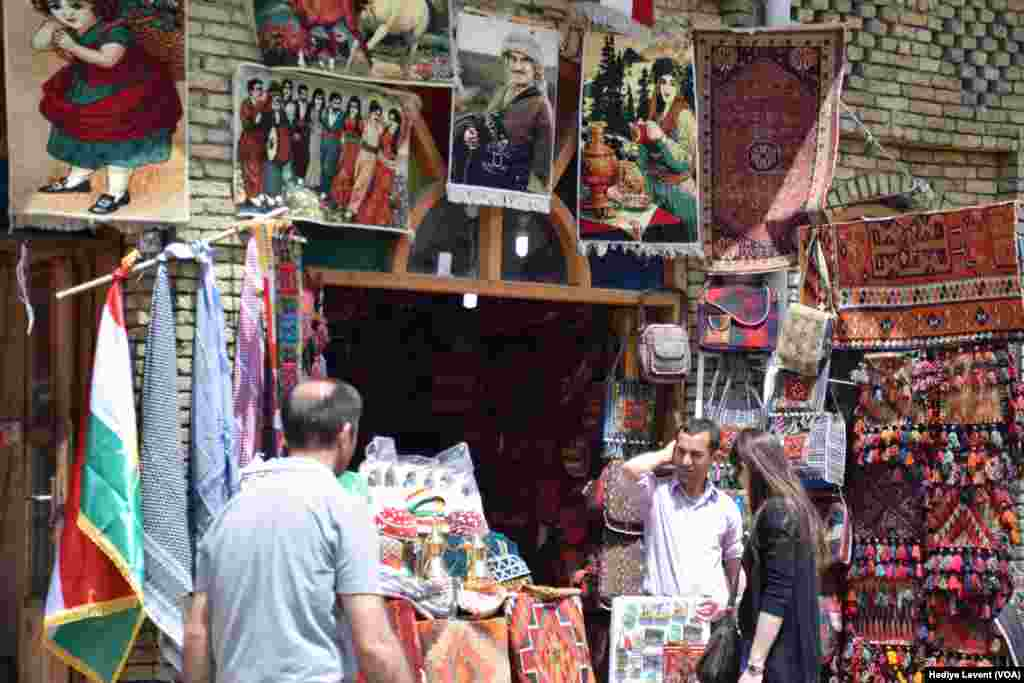 A store in the souq sells traditional patterned fabrics and portraits of important people, in Irbil, Iraq.
