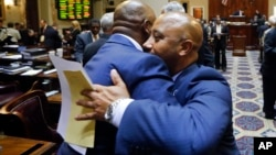 2015年7月9日南卡罗来纳州: 民主党众议员麦克奈特(右)法案通过后和一与会者拥抱