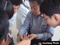 A patient is examined for signs of arsenic poisoning, seen here as hyperkeratosis or a thickening of the skin's outer layer. (Prof. Guifan Sun, China Medical University, Shenyang)