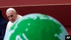 El papa Francisco pasa por un globo que adorna un pastel en honor de su cumpleaños 82, durante una audiencia con niños y familias del dispensario de Santa Marta, una organización de caridad del Vaticano. Diciembre 16 de 2018.