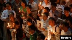 File - Participants hold images of Nguyen Huu Vinh, a dissident blogger, and placards to call for justice in the trial of land protection activist Can Thi Theu and for her freedom, during a mass prayer at Thai Ha church in Hanoi, Vietnam.