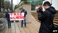 On Dec. 10, 2018, Ada Yu of Vancouver and a man who wished to remain unidentified, hold a sign in favor of the release of Huawei Technologies CFO Meng Wanzhou outside her bail hearing at British Columbia Superior Courts following her Dec. 1 arrest in Canada.