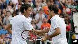 Sergiy Stakhovsky (kiri) menyalami Roger Federer sesudah mengalahkannya dalam putaran kedua (26/6). Kemenangannya yang mengejutkan itu tidak bertahan lama karena Stakhovsky akhirnya tersungkur di tangan Jurgen Melzer dalam putaran selanjutnya.