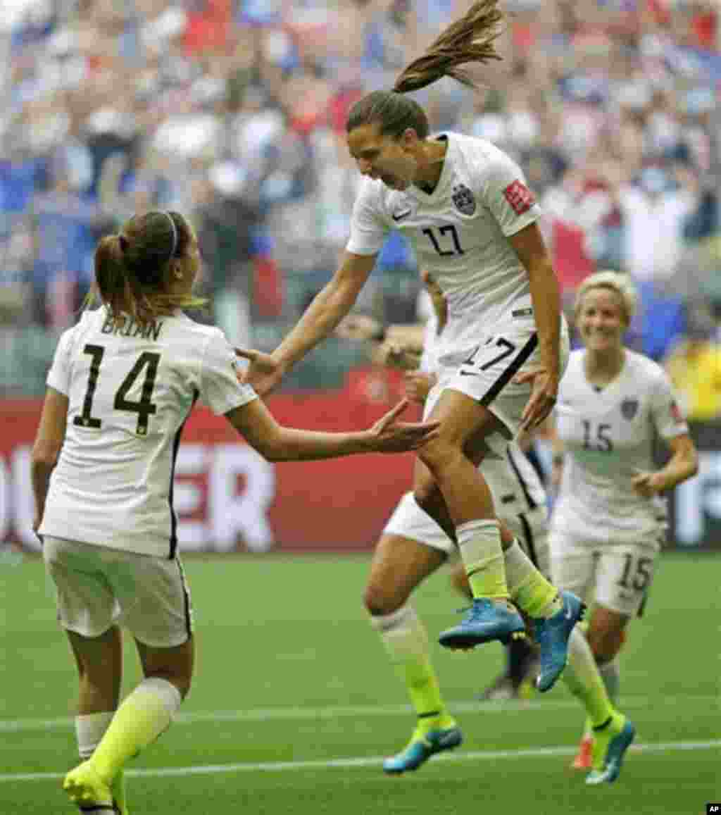 United States' Tobin Heath, center, celebrates with Morgan Brian, left, after Heath scored a goal against Japan during the second half of the FIFA Women's World Cup soccer championship in Vancouver, British Columbia, Canada, July 5, 2015.