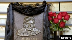 Plakat kuningan hall of fame untuk menghormati penyanyi musik country Johnny Cash terbungkus hitam dengan mawar merah di samping di County Music Hall of Fame and Museum di Nashville, Tennessee, 12 September 2003. (Foto: Reuters)