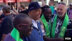 Artiss Russell Simmons (bertopi hitam) ikut meramaikan acara Muslim Day Parade di kota New York, Minggu (25/9). (foto: Ian Umar/VOA).