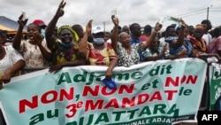 """Les gens applaudissent derrière une banderole """"Adjame dit non, non et non, à un 3e mandat de Ouattara"""", le 26 septembre 2020, à Yopougon, Abidjan."""