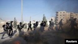 Polisi perbatasan Israel berlari dekat ban yang dibakar dalam bentrokan dengan warga Palestina karena insiden pada hari Rabu di Issawiya, Yerusalem timur, 24 Oktober 2014.