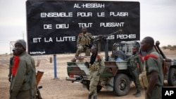"""Malian soldiers are stationed at the entrance of of Gao, northern Mali, Jan. 28, 2013. The sign, a reminder of Islamic extremists, reads """"Al Hesbah, together for the pleasure of God almighty and the struggle against sins."""""""